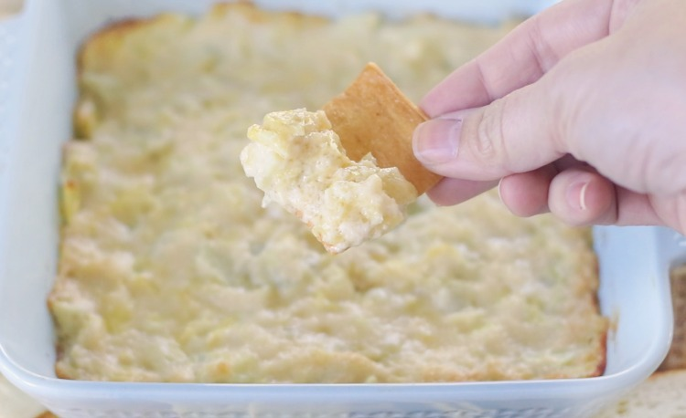 hand holding pita chip dipped in artichoke dip