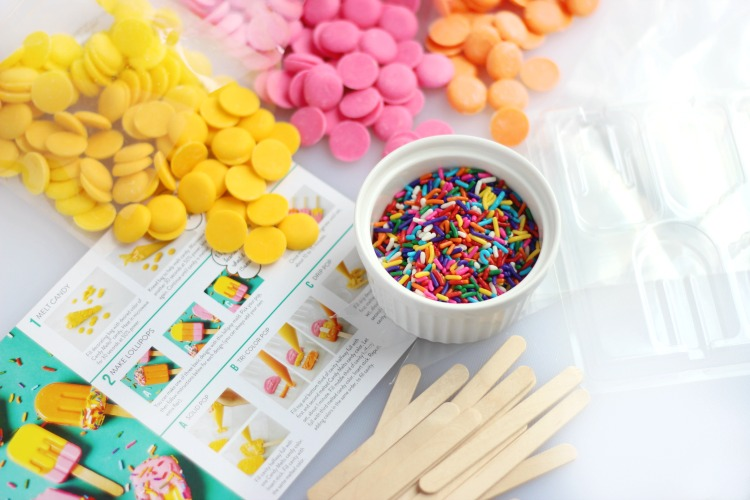 cupcake topper kit ingredients, candy melts, sprinkles, popsicle sticks on table