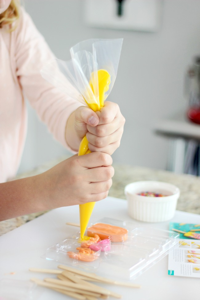 child piping melting candies into popsicle mold