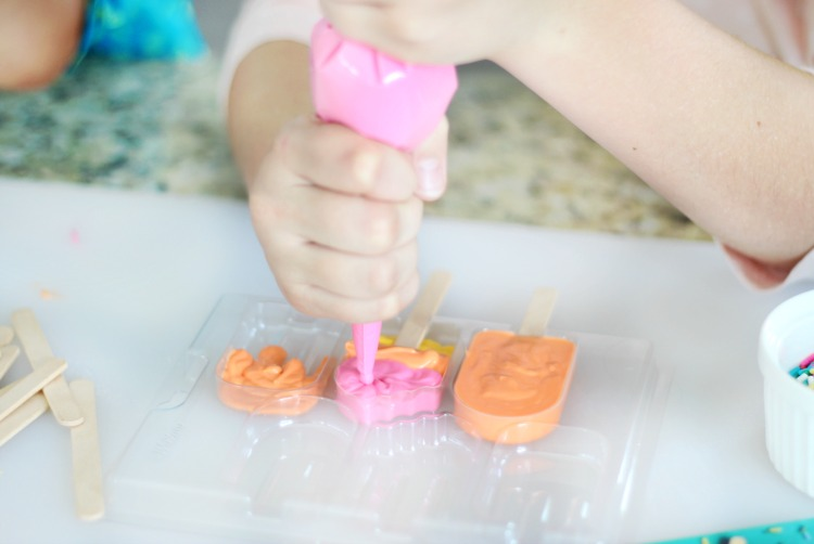 child piping melting candies for lemonade cupcakes into mold