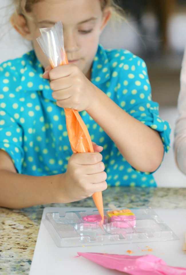 child piping melting candies into mold