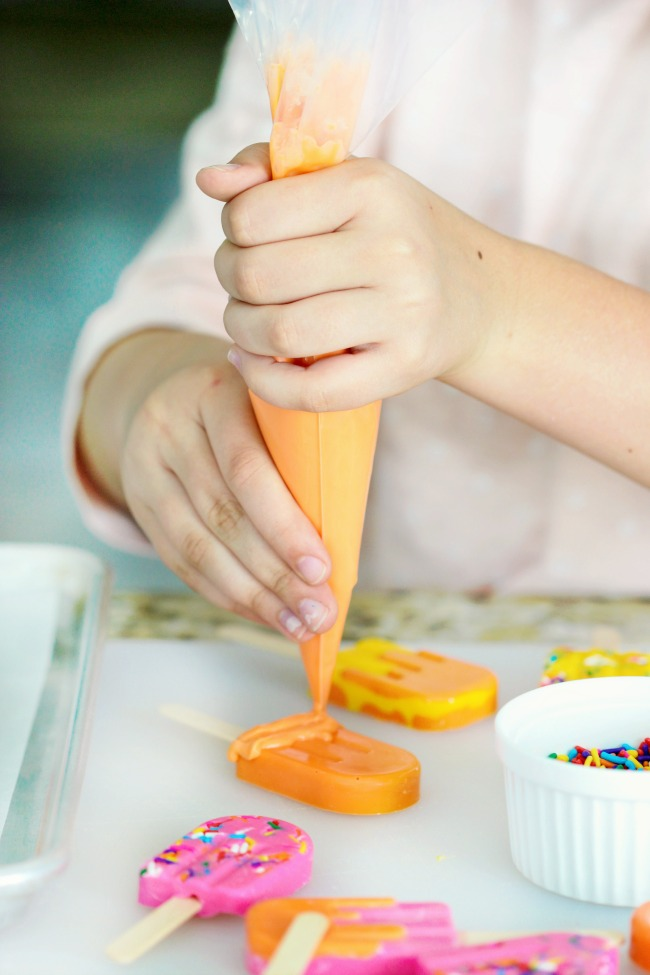 child adding sprinkles to candy popsicle