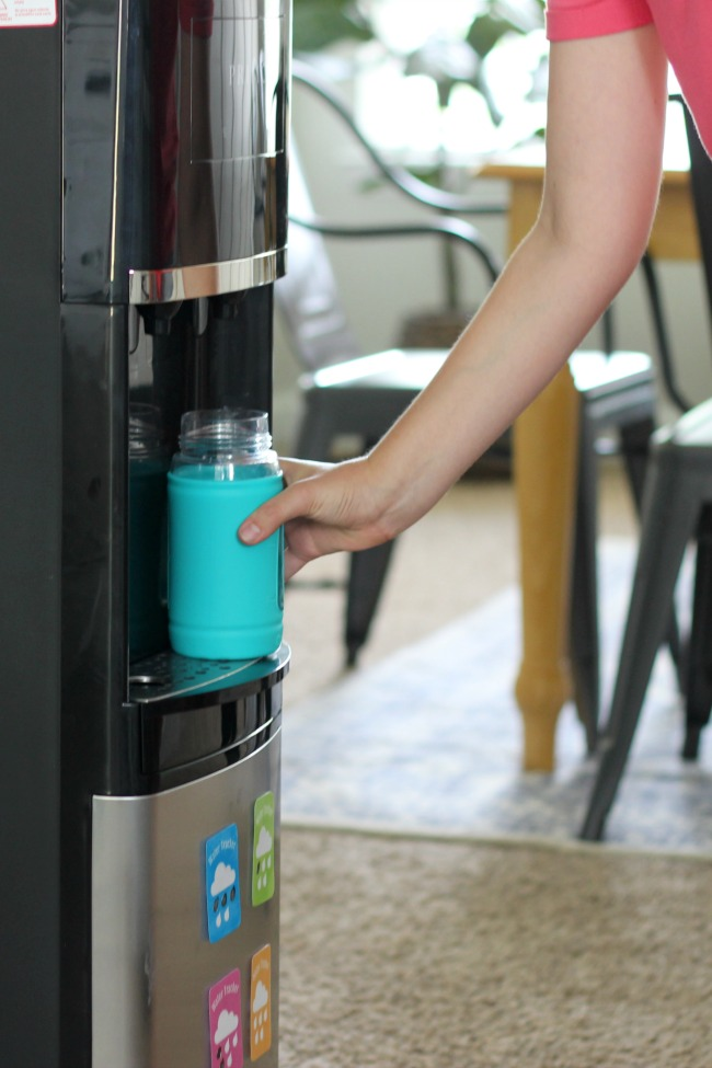 child filling reusable water bottle