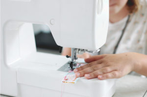 child sewing laundry bag on sewing machine