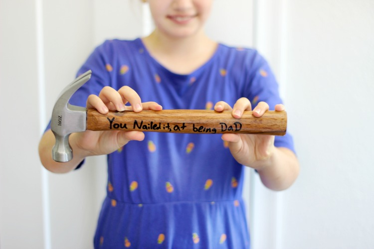 "child holding diy personalized hammer that says ""You Nailed it at being Dad"""