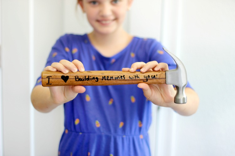 "child holding diy personalized hammer that says ""I (heart) building memories with you!"""