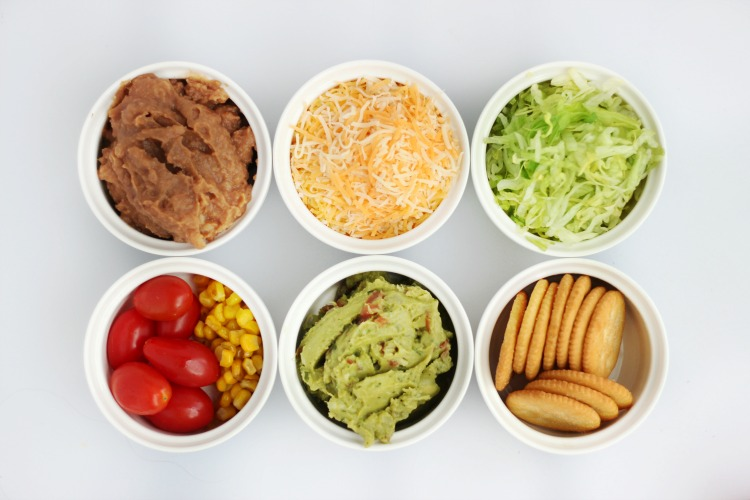bowls with refried beans, cheese, lettuce, tomatoes, corn, guacamole and crackers