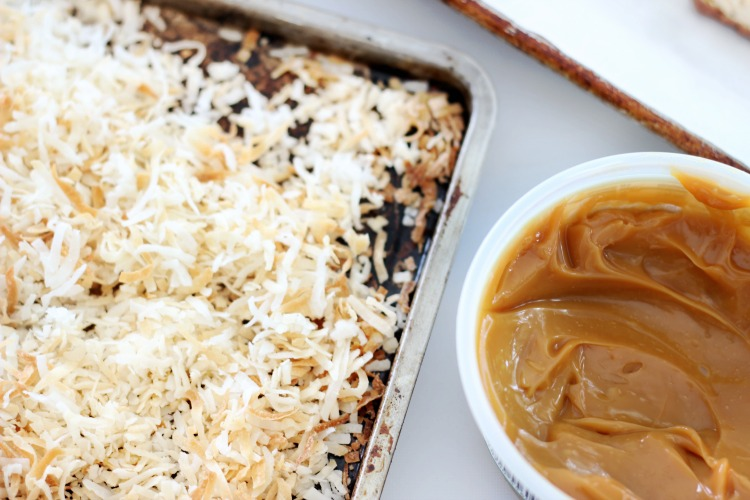 pan with toasted coconut and open container of caramel sauce