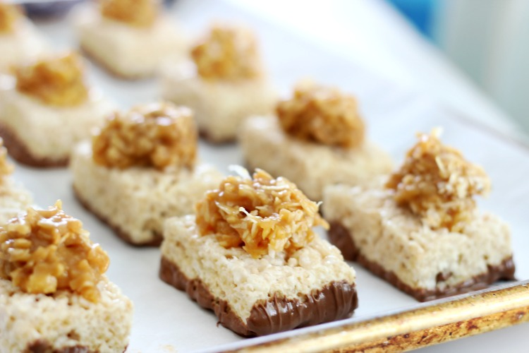 Rice Krispies treats topped with caramel and coconut mixture on baking sheet