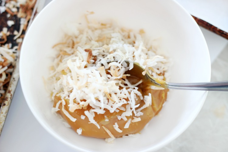 bowl with spoon stirring toasted coconut into caramel dip
