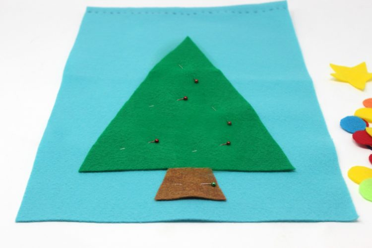 blue felt with green triangle and brown rectangle for tree and tree trunk