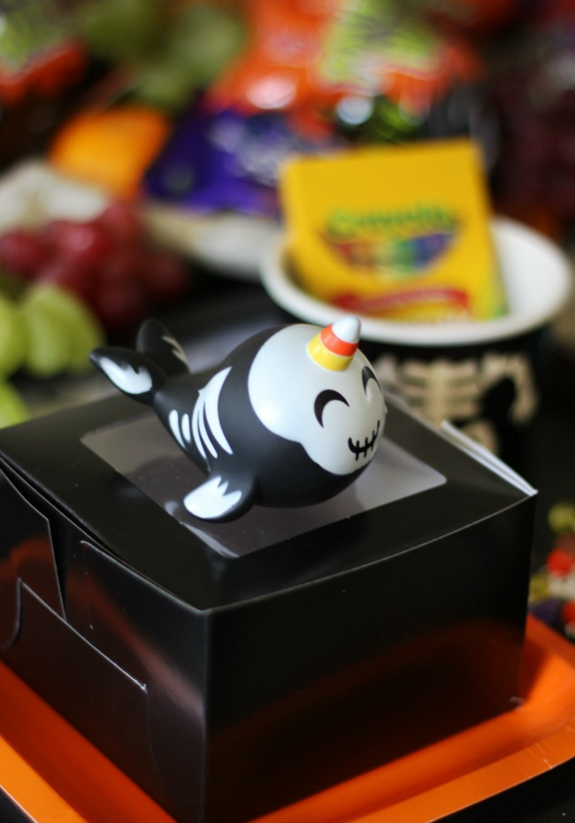 black treat box with Halloween narwhal toy on top for party favor