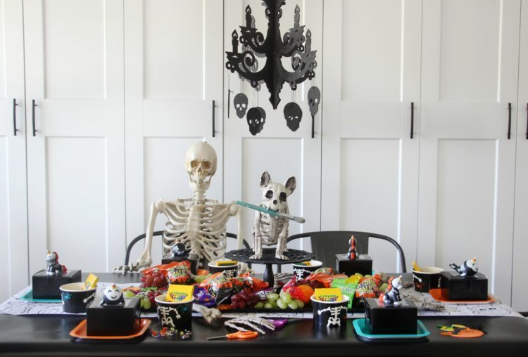 table with skeletons, party supplies, black table cloth and chandalier (finished party)