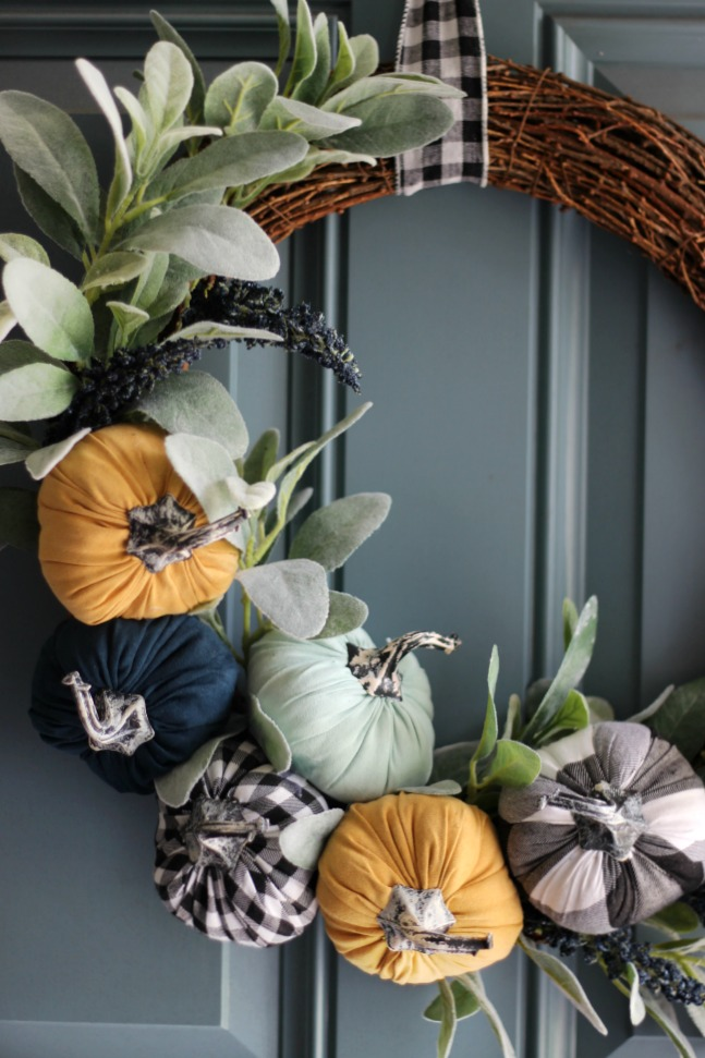 pumpkin wreath with buffalo check ribbon hanging on door
