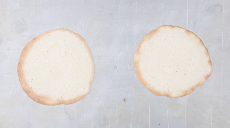 2 baked fortune cookies flat on baking sheet
