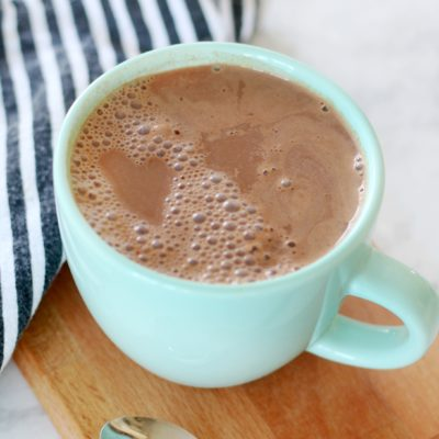 mug of cocoa on cutting board with napkin
