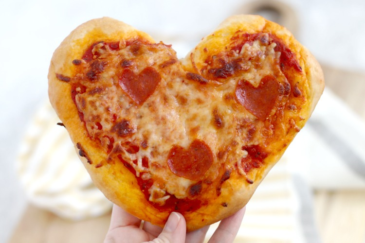 mini heart pizzas held in hand