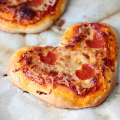 mini heart pizzas on parchment paper