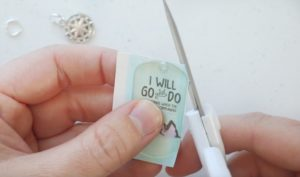scissors trimming around acrylic sticker