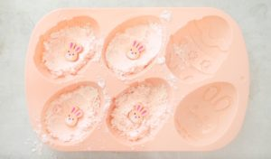 soap mold with bath bomb mixture and bunny toy in each bath bomb cavity