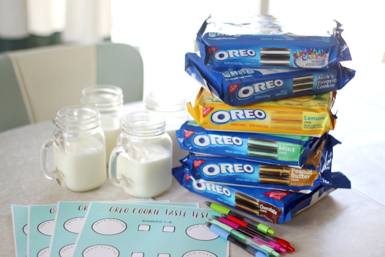 table with stack of oreo packages, pens, printable worksheets and glasses of milk