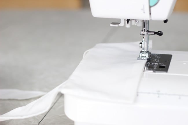 sewing machine stitching across white fabric