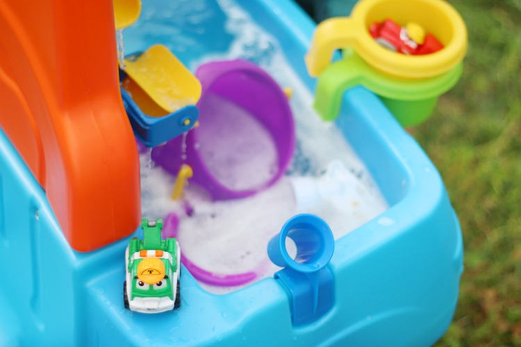 green toy truck next to sudsy water in water table