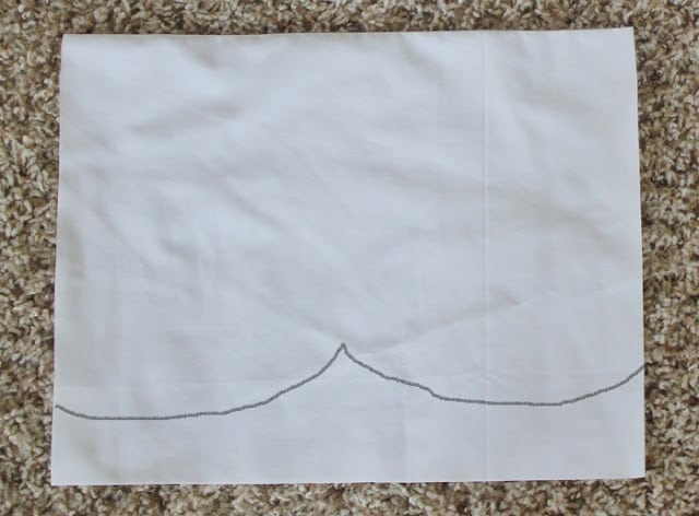 white fabric with a black line drawn to show how to cut scalloped edge