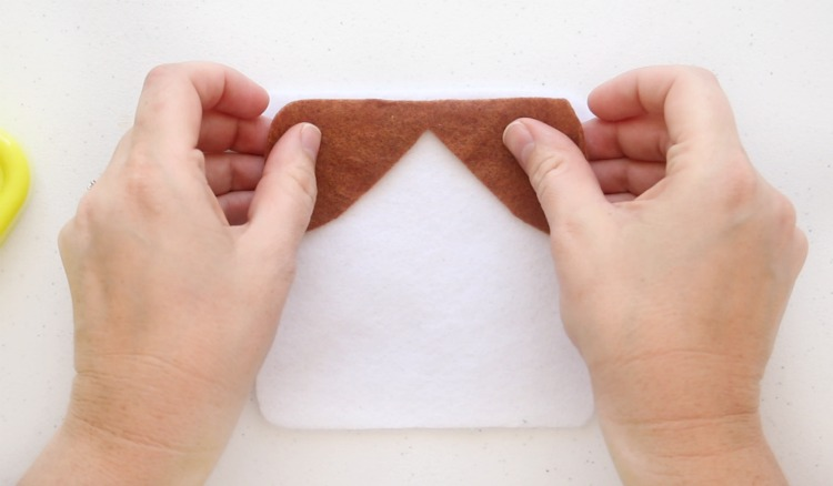 pinning brown dog face to white felt square