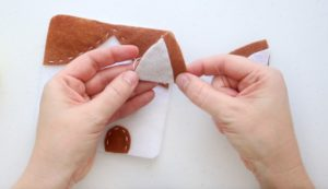 hand stitching two felt triangles for dog ears
