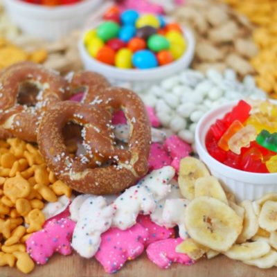 pretzels, goldfish crackers, animal crackers, banana chips and candy on wooden board