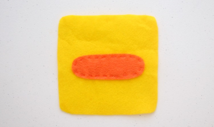 yellow square of felt with duck beak stitched on