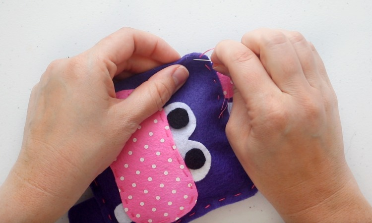 sewing hippo softie closed with a needle and thread