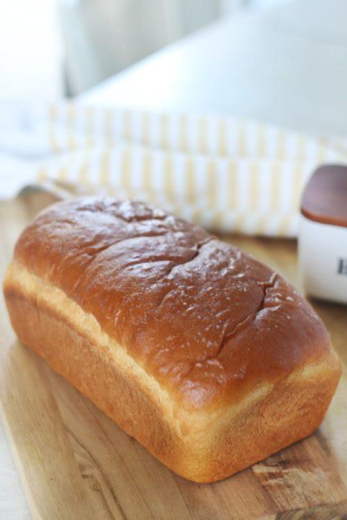 loaf of honey wheat bread on cutting board