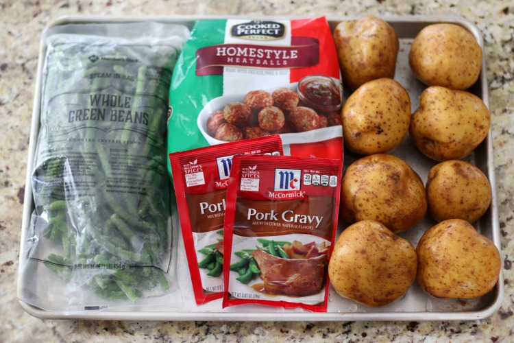 ingredients for ikea copycat swedish meatballs: tray with gravy packets, green beans, potatoes and frozen meatballs