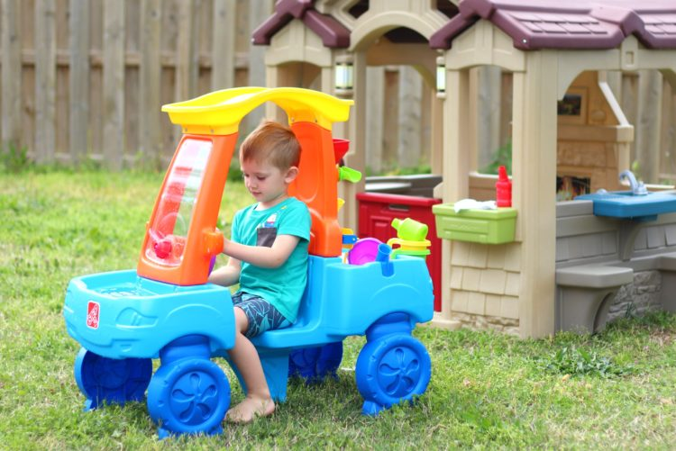 child sitting in car water table