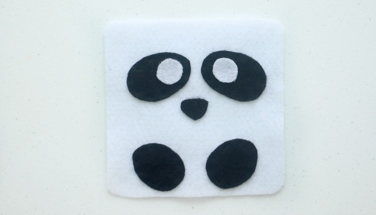 white square of felt with black ovals of felt for eyes and feet