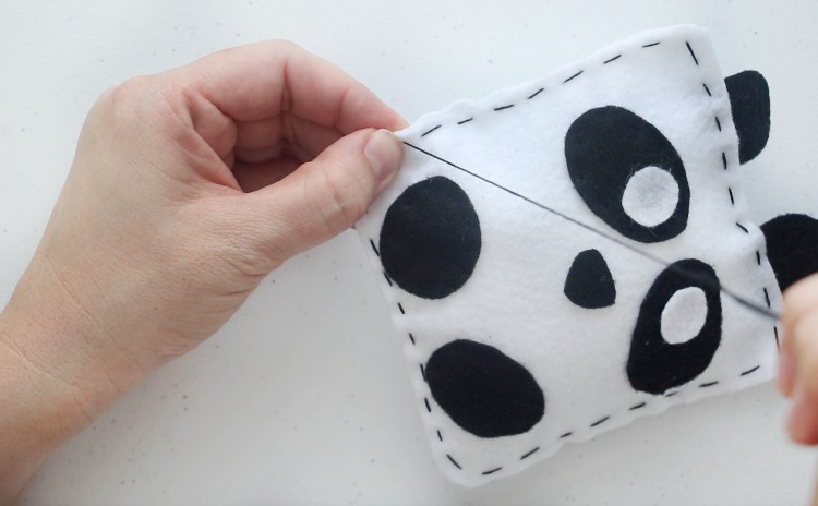 stitching the opening closed with black thread