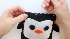 hands stitching penguin closed