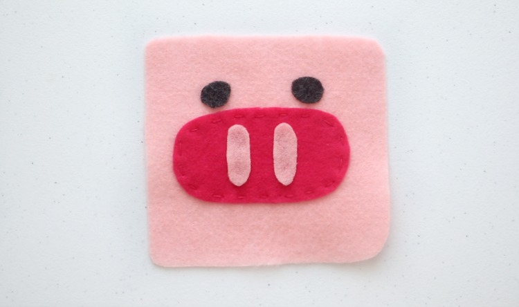 pig softie face glued onto pink felt square