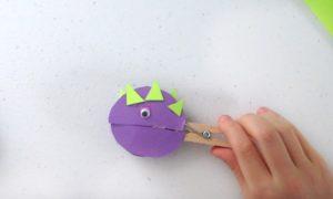 child holding clothespin dinosaur