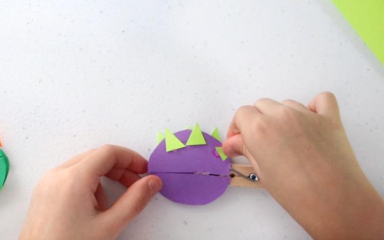 child gluing spikes onto dinosaur