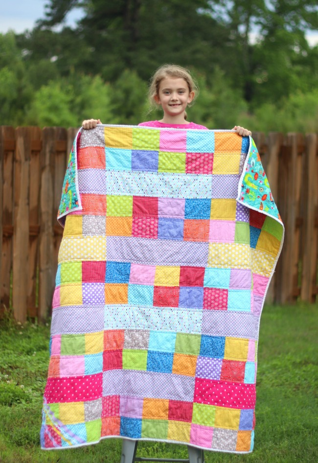 girl holding finished kids scrappy quilt