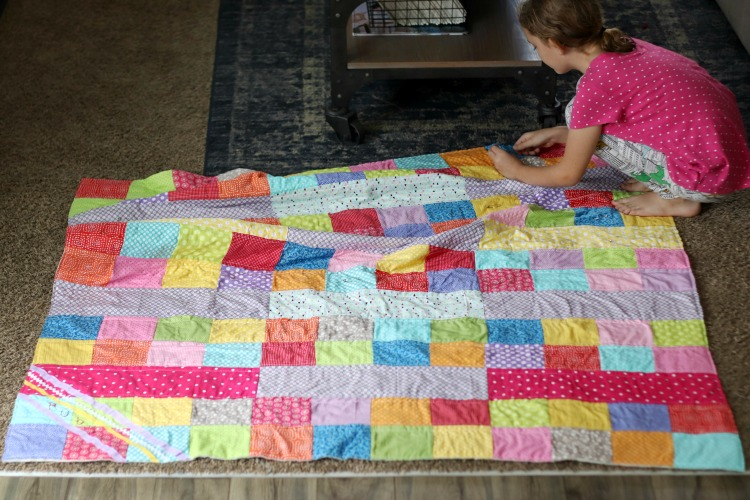 girl cutting off loose threads from quilt