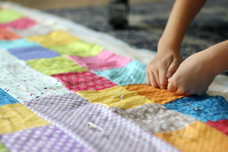hands pinning safety pins to quilt top