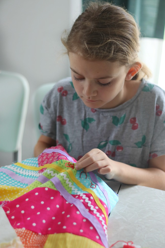 girl embroidering name onto quilt top