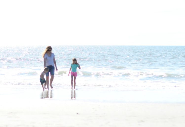 mom and kids walking on beach