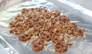 baking sheet lined with foil with pretzels and chopped peanuts