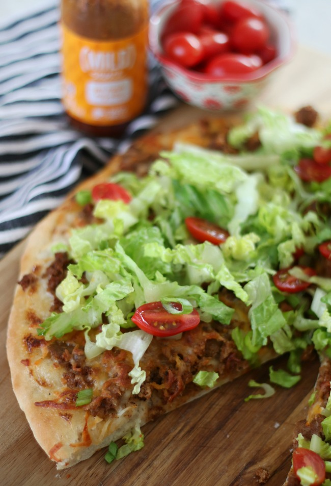 taco pizza with one slice cut out
