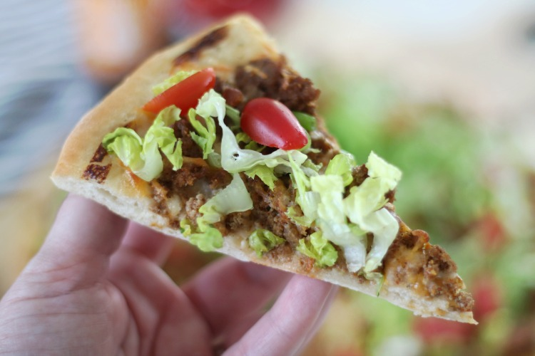 hand holding slice of taco pizza